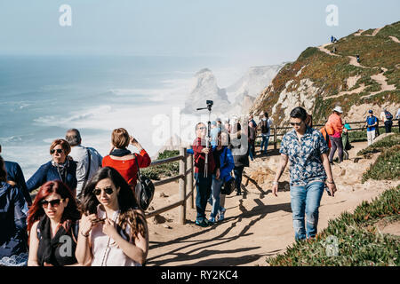 Portugal, Sintra, June 26, 2018: A group of people or tourists admire sights and take pictures and take selfies at Cape Roca. - Stock Photo
