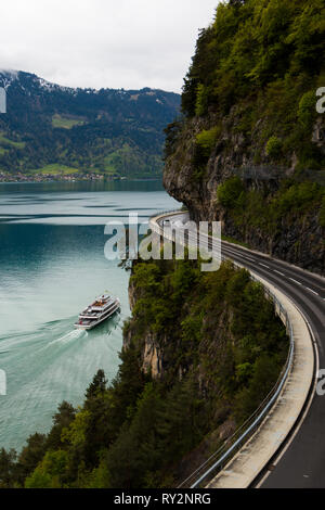 Winding mountain road at lake Thun in Switzerland with a boat passing by, car on the road - Stock Photo