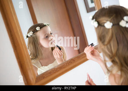 Young bridesmaid putting lip gloss on in front of a mirror - Stock Photo