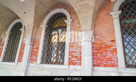 The big windows with grills on the buildings lining on the side of the grand canal in Venice Italy - Stock Photo