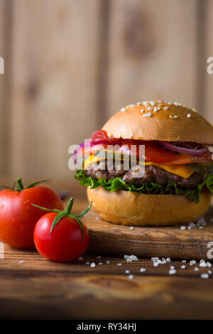 Classic american cheeseburger on a wooden board with tomatoes and onion. - Stock Photo
