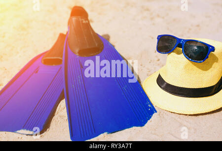 Blue fins hat and sunglasses on the sandy beach. Bright outside. Sun shines. - Stock Photo