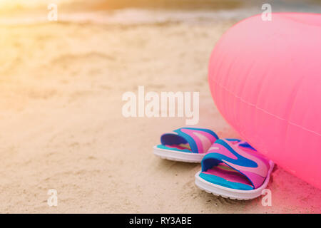 Flip-flops lying on beach under pink swimming circle. Summer vacation concept. Sun shines bright. Cut view. - Stock Photo