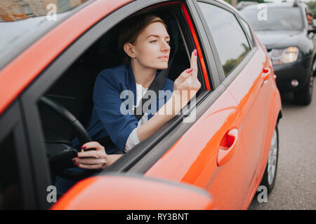 A woman feels stress on the road. Shows the fact in the window. Big Traffic jams. Business woman is late for work - Stock Photo