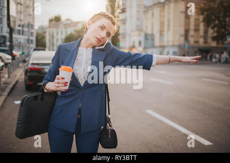 oung stylish businesswoman with coffee cup catching a taxi. Woman doing multiple tasks. Multitasking business woman. - Stock Photo