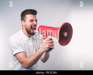 portrait of man shouting using megaphone over background Nerd is wearing glasses. - Stock Photo