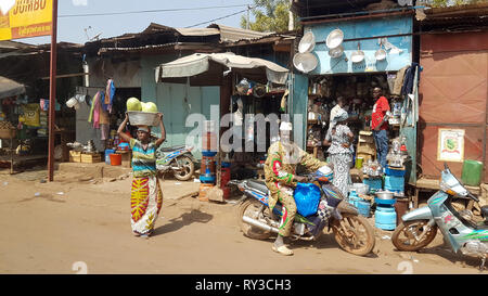 BAMAKO, MALI - DEC 19, 2016: Generic shopping street of the Bamako with people selling on the streets diverse object - Stock Photo