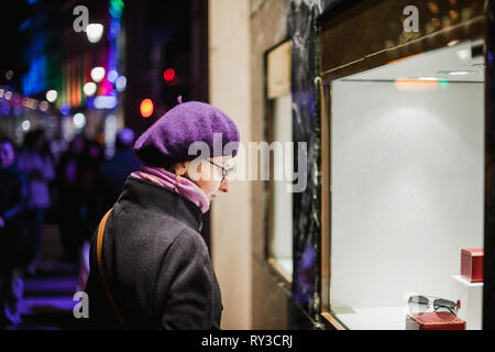 French elegant woman search for the Christmas gift in Jewelry shop from the French Street - searching for the best present during Christmas holidays - Stock Photo