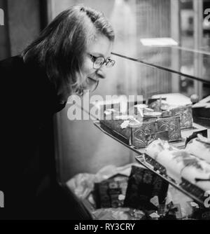 Woman buying sweets a the patisserie bakery store window in French city during Christmas winter holidays  - Stock Photo