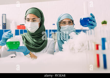 female muslim scientists holding flasks while experimenting with dry ice in chemical laboratory - Stock Photo