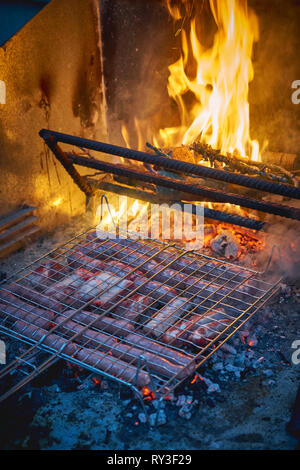 A selection of pork meat cuts including ribs, sausages and pork belly cooked on a barbecue. Portrait format. - Stock Photo