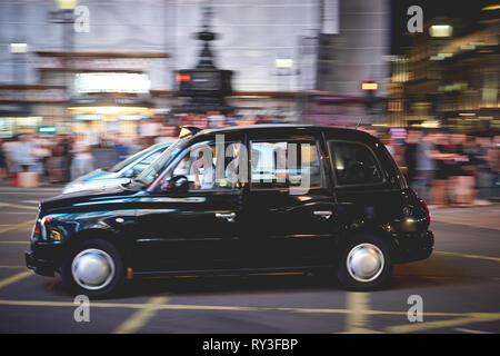 London, UK - August, 2018. A taxi in Piccadilly Circus at night. Black cabs are the most iconic symbol of London as well as Red Double Decker Buses. - Stock Photo