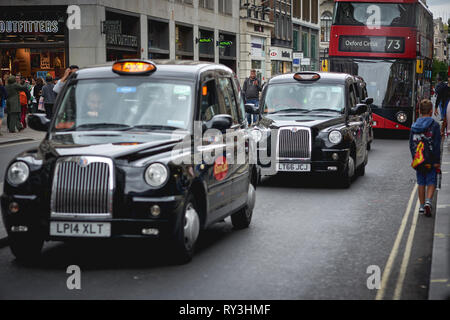 London, UK - August, 2018. Iconic black cabs and red buses in central London. - Stock Photo