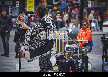 London, UK - August, 2018. A street rock musician performing outside Tottenham Court Road Underground station in a crowded Oxford Street. - Stock Photo