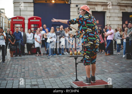 London, UK - September, 2018. A street artist entertaining a crowd of tourists in Covent Garden. - Stock Photo