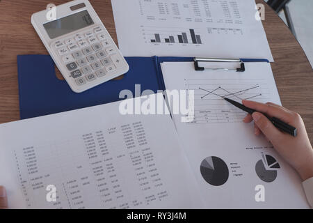 close-up hand of people working in office, studying using calculator and writing something with documents and chart on table - Stock Photo