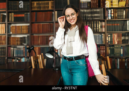 Brunette student girl in the white shirt wearing glasses standing with pink backpack at the library - Stock Photo