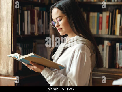 Clever student girl standing near the window at the library and reading book for exam - Stock Photo