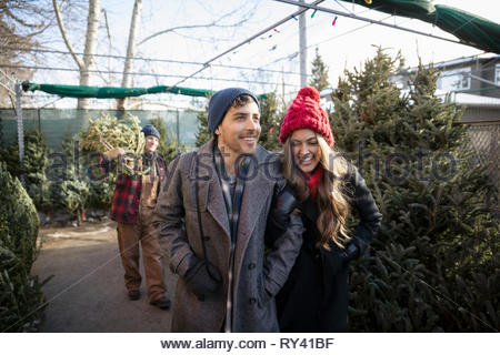 Happy couple shopping for christmas tree at christmas market - Stock Photo