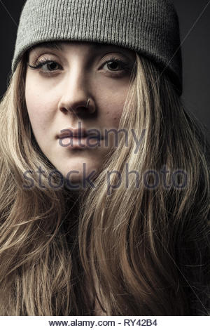 Portrait confident beautiful young blonde woman with nose ring wearing beanie - Stock Photo