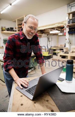 Senior carpenter using laptop in woodworking shop - Stock Photo