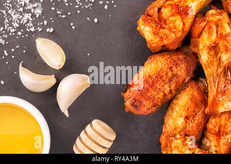 Chicken wings with honey and garlic on a black slate in background. - Stock Photo