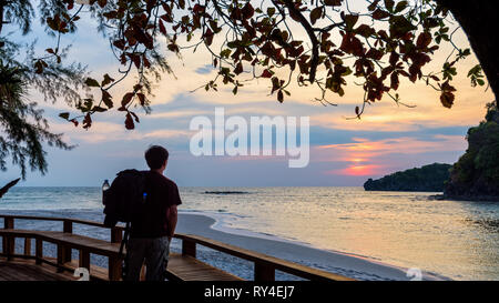 One man traveler with a backpack is standing looking at the sunset. beautiful nature landscape of colorful the sun on the sky at Koh Tarutao island, S - Stock Photo
