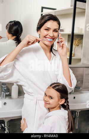 daughter hugging mother brushing teeth and talking on smartphone in bathroom - Stock Photo