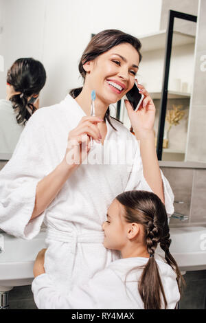 daughter hugging mother talking on smartphone in bathroom - Stock Photo
