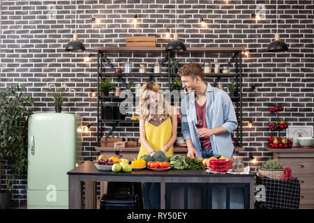 Blonde-haired woman with wavy hair enjoying cooking time with her man - Stock Photo