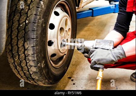 Auszubildender schraubt ein gewechseltes Rad eines Autos wieder an oder ab. Mit einem Pressluftschrauber. - Stock Photo