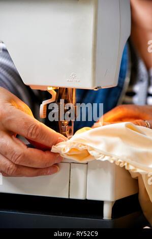Nahaufnahme einer Schneiderin die an einer Naehmaschine den Stoff unter der Nadel fuehrt beim naehen. - Stock Photo