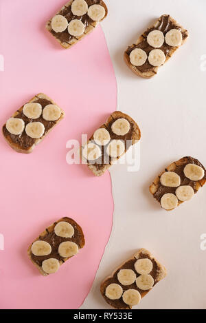 High angle view of toasted breads with chocolate butter and banana slices on table - Stock Photo