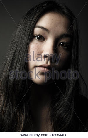 Close up portrait confident beautiful teenage girl with long black hair, brown eyes and freckles - Stock Photo