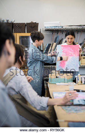 Teacher and student presenting painting in art class - Stock Photo