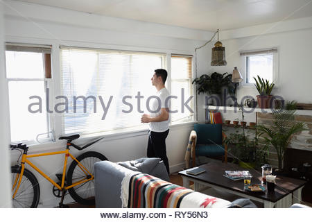 Thoughtful young Latinx man looking out sunny living room window - Stock Photo