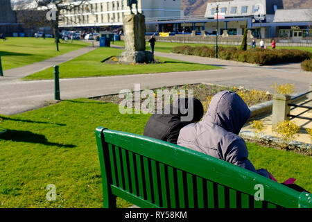 A couple sitting on a bench with their hoods up seen from behind in fort william town center - Stock Photo