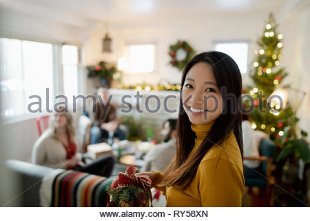Portrait confident woman with friends in christmas living room - Stock Photo
