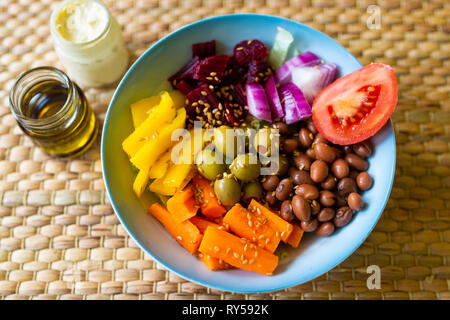 A vibrant vegan buddha bowl filled with colourful vegetables and pulses - Stock Photo