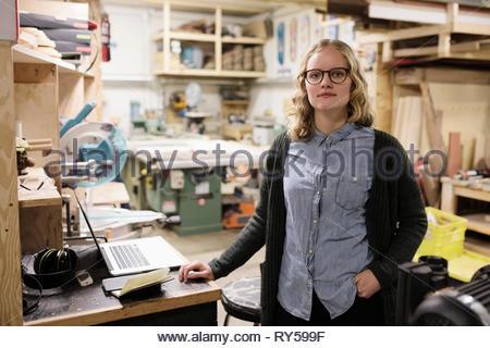 Portrait confident female artist in woodworking workshop - Stock Photo