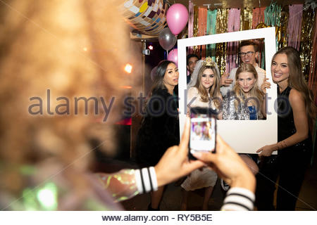 Woman with camera phone photographing friends posing for photo booth at party - Stock Photo