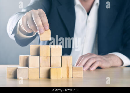 Business man puts next stone on complex structure made from wooden blocks; career or achievement or complex project management concept, blue toned wit Stock Photo