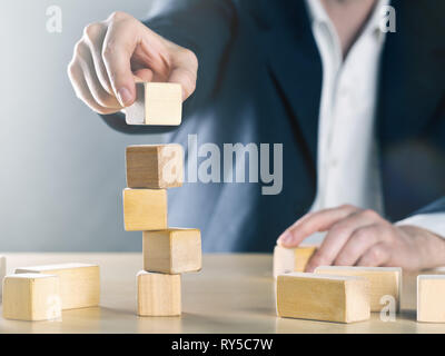 Business man puts next stone on shaky tower structure made from wooden blocks; career or achievement or complex project management concept, blue toned - Stock Photo