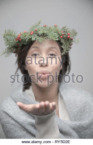 Portrait beautiful young brunette Jamaican woman wearing christmas wreath on head and blowing a kiss - Stock Photo