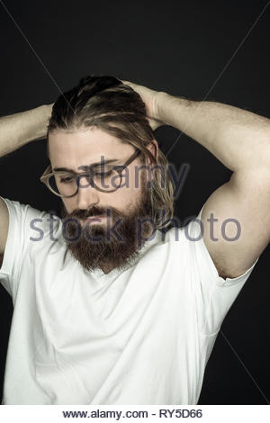 Young handsome hipster man with beard and hands in head - Stock Photo