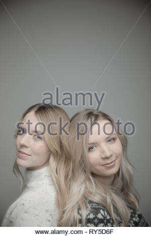 Portrait confident beautiful young blonde women standing back to back - Stock Photo