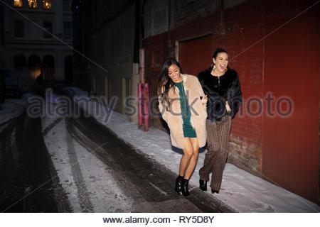 Women friends leaving nightclub, walking on snowy urban street - Stock Photo