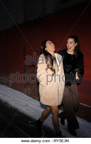 Laughing women friends walking in snowy alley at night - Stock Photo