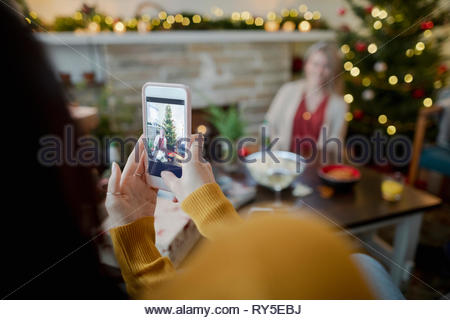 Woman with camera phone photographing friend in christmas living room - Stock Photo