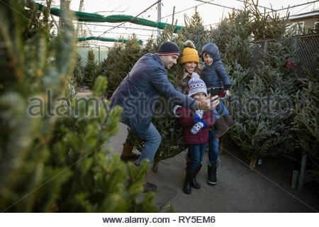 Family taking selfie, shopping for christmas tree at christmas market - Stock Photo